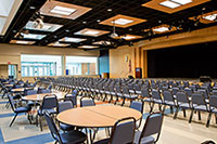 Gaiser student center showing tables in back of room and chairs arranged in rows in the front of the room, facing the stage.