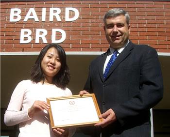 Clark College President Robert K. Knight congratulates scholarship recipient Trang Tran