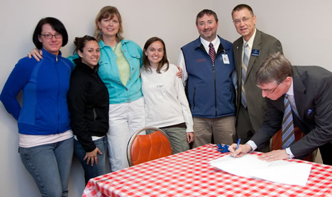 Left to right:�Clark College students Nova Sehorn and Adrienne Sousa, Health and Physical Education Professor Lisa Borho, student Tiffany Bunn, and Dean of Health Sciences Blake Boweres welcome Concordia University Profess or of Exercise & Sport Science Dr. Joel Schuldheisz and (signing the agreement) Concordia Provost Dr. Mark Wahlers.
