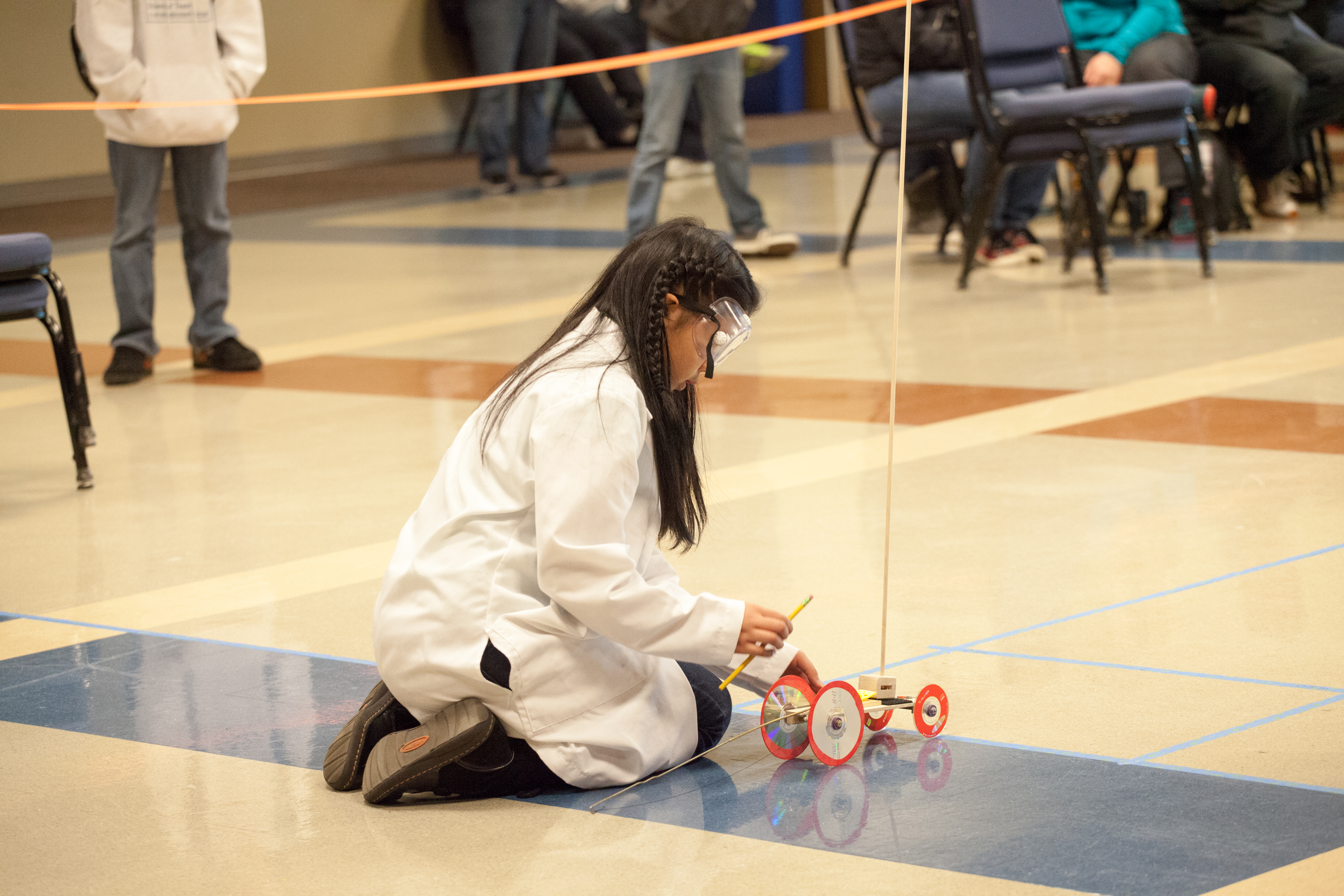 Young woman in white lab coat crouched down with small robotic vehicle.