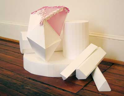 arrangement of paper sculptural pieces in geometric shapes