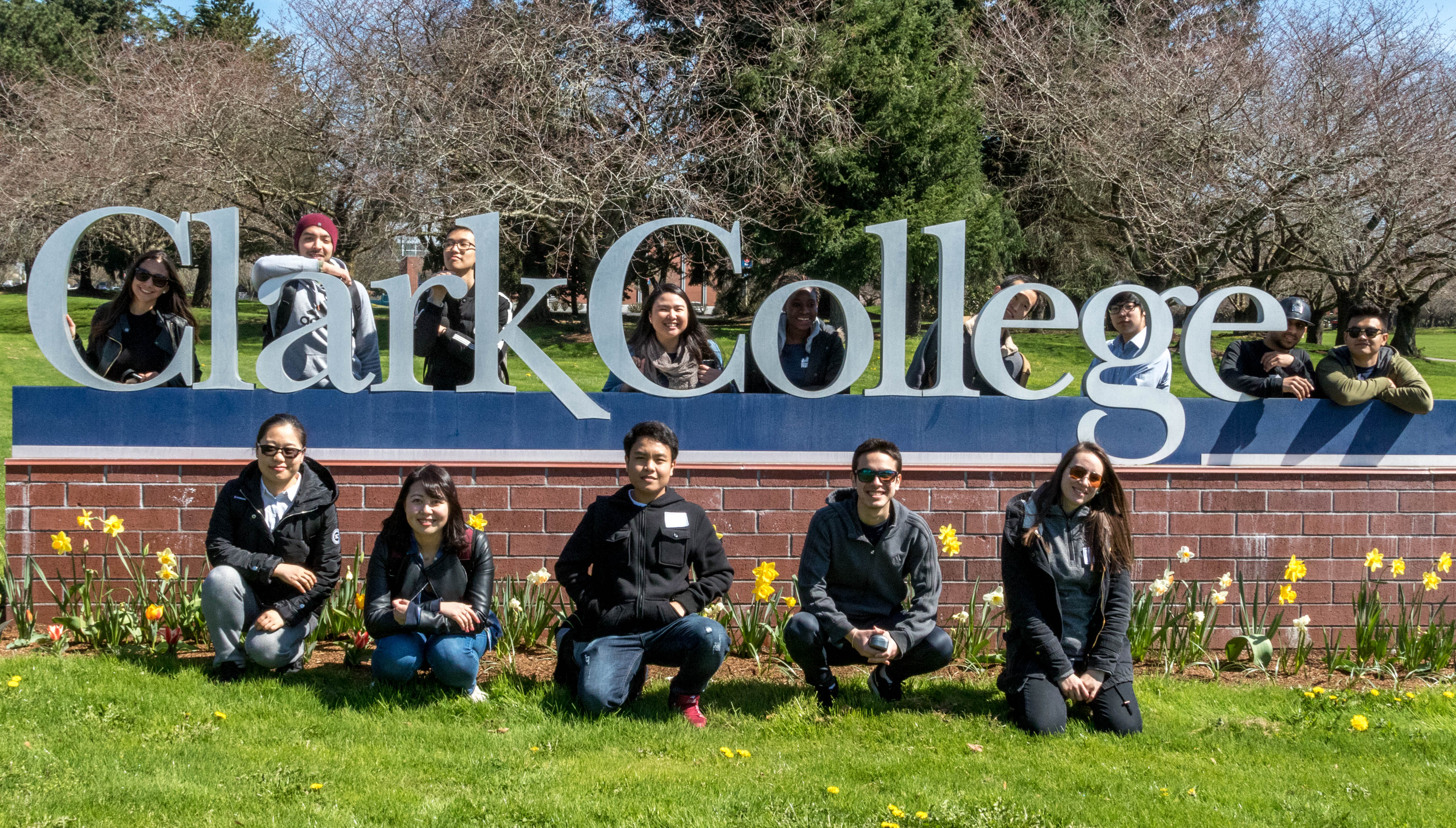 International students pose with the Clark College campus sign