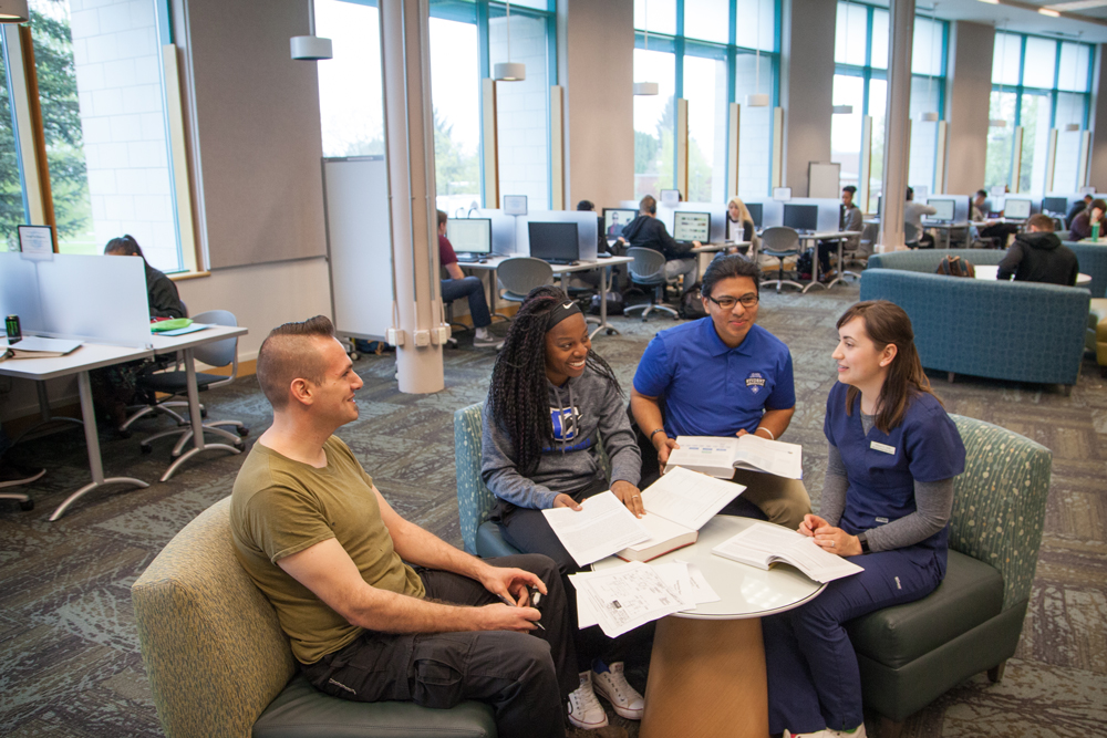 Four students talking, smiling while sitting around a desk with text books and papers in Cannell Library