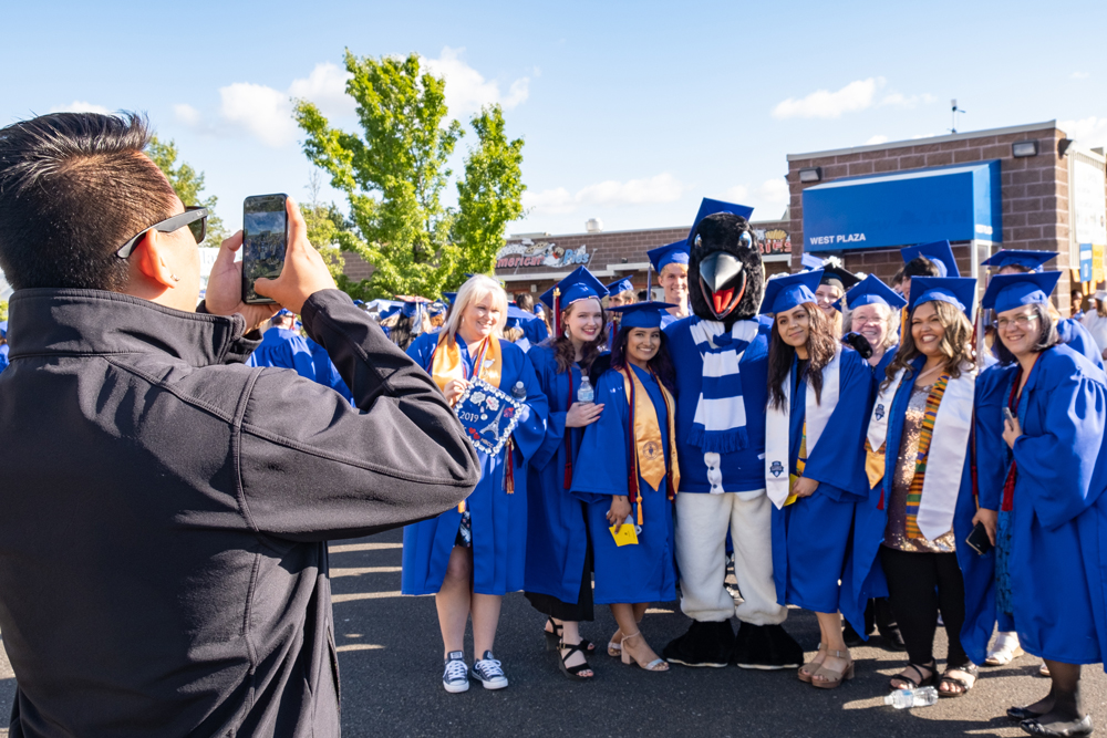 Oswald with a lot of graduates smiling at a man taking their photograph with a phone.