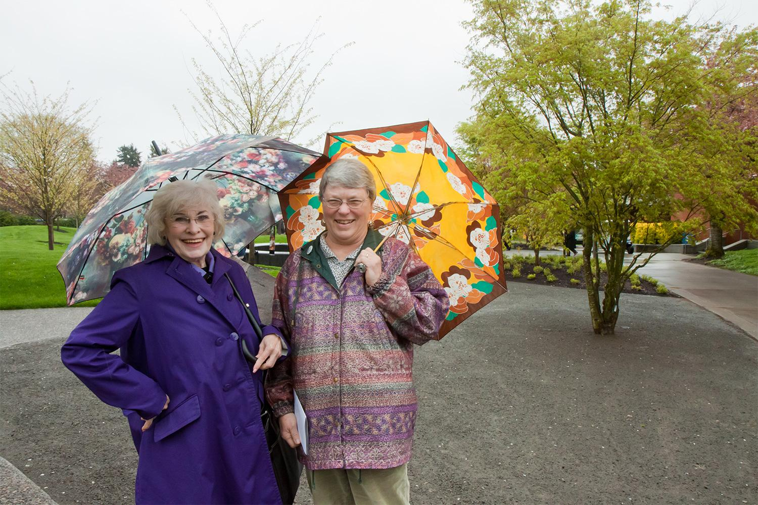 Two community members stand with umbrellas in the Royce Pollard Japanese Garden
