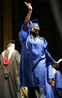 Excited Clark College graduate waves to the audience