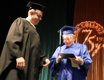 Clark College President Robert K. Knight presents a diploma to graduate Wilbert Kalmbach