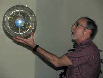 Dick Shamrell holding a globe featuring the stars
