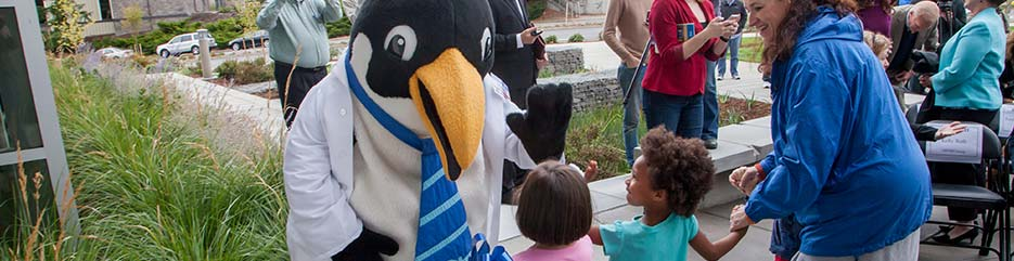 Oswald, Clark's mascot penguin, with some young children.